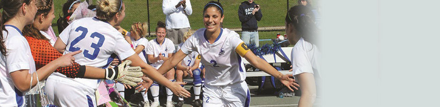 A starter on the women's soccer team slaps hands as she comes through her teammates.